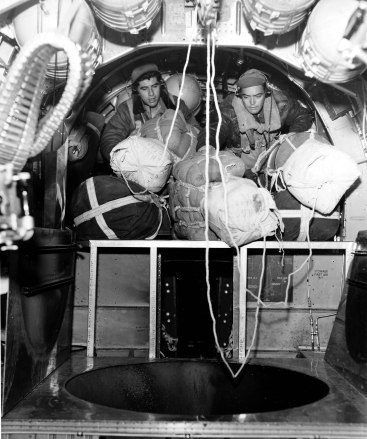 T/Sgt Charles Locasto, NY and S/Sgt John Padgett, NC, both from 885th BS, attach parachute drop packages to the static line on board of their plane over Italy. 15 Feb 1945.