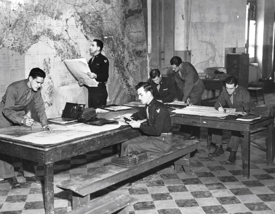 Navigators of the 885th BS plot the course for their next mission in Northern Italy. Brindisi, Italy. 15 Feb 1945.